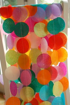 What do you think about hanging tissue paper garland similar to this, but in your colors, and string lights from the ceiling to the floor on the wall in between the two entrances in the foyer? We could put the sign in table in front of it and do a few simple floral arrangements for the table. The light from the twinkle lights would be really pretty with the delicate tissue paper, I think.