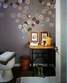 Jellyfish wallpaper from Trove sets off an antique sewing table and wood bucket in a remodeled powder room.