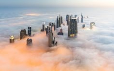 Skyscrapers emerge through a blanket of fog and cloud in Dubai as seen from the top of the world's tallest building, the Burj Khalifa