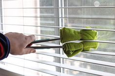 You can make a great DIY substitute for those blind cleaning tools you see in stores by attaching a couple of microfiber cloths to a pair of tongs with some clips or rubber bands.