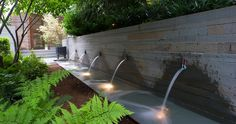 STEPHEN STIMSON ASSOCIATES | WOODLAND RESIDENCE Contemporary water feature with stainless steel spouts. Pinned to Garden Design - Water Features by Darin Bradbury.