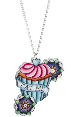"EAT ME CAKE ALICE NECKLACE    Add a bit of whimsy to your jewelry box with a Alice inspired necklace! This silver chain features an acrylic, die-cut full color cupcake, flowers & ""Eat Me"" in a banner.    $15.00"