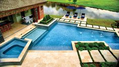 This striking geometric pool includes a glass-finished tanning shelf, elevated spa, jet decks, and travertine deck with stepping stones. Ewing Aquatech, Baton Rouge, Louisiana http://www.luxurypools.com/builders-designers/ewing-aquatech.aspx