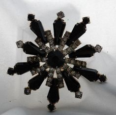 Antique Jet Black Glass Star Burst Brooch with White Rhinestones .    Lovely and dramatic faceted jet black glass round and tear drop stones with white rhinestones.  However at the end of each tear...