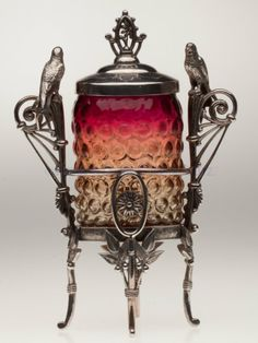BLOWN-MOLDED HOBNAIL AMBERINA PICKLE CASTER, brilliant fuchsia to amber, jar base with 18 petals and a polished pontil mark, ornate Rogers Bro. #122 quadruple-plate stand with birds. Probably Mt. Washington Glass Co. Fourth quarter 19th century.