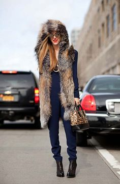 Joanna Hillman looks straight off the runway in a fur hooded vest by The Row and a navy jumpsuit.    #streetstyle #newyorkfashionweek #fashion #fashionweek #style #harpersbazaar #mrnewton