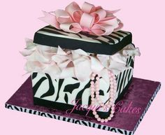 One tier Zebra print, black and white fondant gift box cake. The Zebra print lid has a lovely pastel pink fondant bow wedding cake topper made to look like a present with a bow. Under the lid is sugar paste gift wrapping tissue paper and pink gum paste pearls. The cake is made to look like a wedding cake gift box. From Jacqui's Cakes