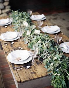 Fresh greenery for a table runner makes for sweet simplicity. White plates and antique silverware paired against worn wooden tables create a romantic table setting. Photo by Scott Michael Photography. Via @100 Layer Cake
