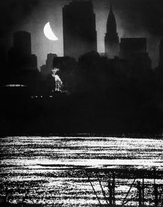 A view from New Jersey of the moon shining over Manhattan's RCA and Chrysler buildings, 1946.