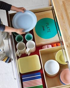 "They say: ""This idea is a great way to teach your kids where everything goes. Designate a low drawer for your children's plastic dishes. To remind them of what goes where, paint and label a silhouette of each dish.""  I say: Am convinced that the cabinet of mix-and-match sippy cups and water bottles teaches them survival skills."