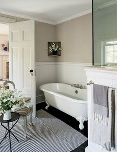 An antique chair rests on a striped rug in the master bath.
