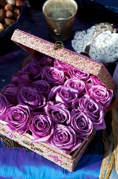 Purple rosebuds are clustered into a whimsical fabric-covered box for a unique centerpiece display.