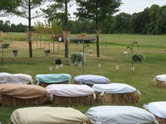 Barn yard wedding with garden stakes & hay bales covered in fabric.