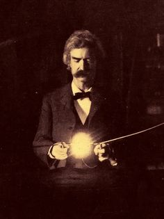 "Mark Twain in Nikola Tesla's apartment, New York 1894    The high-voltage current is being passed through the human body to bring the lamp to incandescence. Tesla's friend, Mark Twain, is holding the loop above the resonating coil. Tesla is in the background.    Originally published as part of an article by T.C. Martin called ""Tesla's Oscillator and Other Inventions"" that appeared in the Century Magazine (April 1895)"