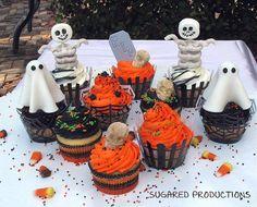 Cupcakes con cubiertas naranja y negro, wrappers y figuras