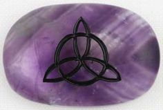 "Sculpted from Amethyst, this gratitude stone has been engraved with the tangled image of the Celtic Triquetra on its front facing. Place it in your palm and trace the lines with your thumb to help focus your intent, will, and energy to any purpose. This gratitude stone measures approximately 1 1/2"" in length."