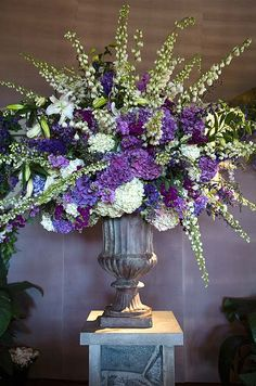 Branches of white delphinium emerge from an oversized arrangement of white and purple hydrangeas.
