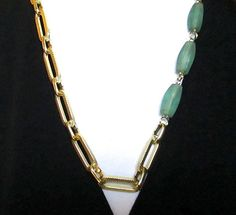 $19.00.  VINTAGE from my favorite vendor.   Three large cylinders of frosted aqua glass are on the side of the bulky chain, adding a beautiful color and design to the gold tone necklace. The