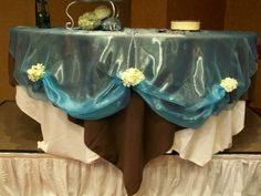 Ivory tablecloth with a dark brown overlay, covered with an organza turquoise overlay. I really like the flowers around the edge!