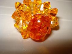 """Handmade with bicone """"crystal"""" beads in two different shades of orange and one large oval bead with """"sparkles"""" inside.Approximate Measurements: One size fits most - made with stretch cord."""