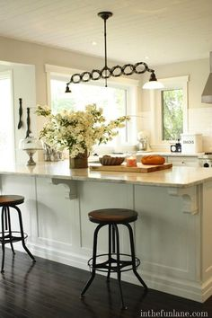 source: In the Fun Lane Amazing kitchen with tan walls paint color, subway tiles backsplash, white kitchen cabinets with marble countertops, kitchen island peninsula and vintage stools