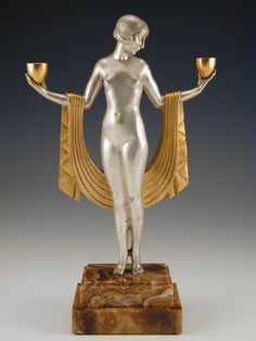 Designer: Pierre Le Faguays; Description: Bronze figure on stepped marble base. The silvered body with classic Art Deco gilded drapes & cups.  Country of ManufactureFrance, c.1930