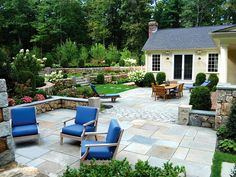 Mix Stonework  A combination of different stones gives this outdoor space a customized and visually interesting look. Stacked New England fieldstone is used throughout the backyard to create seating walls on the patio and retaining walls that terrace the yard. Antique cobblestone divides the bluestone patio to create a separate dining room and conversation area in front of the fireplace, and reclaimed granite is used to make the steps and pillars. Design by a Blade of Grass Landscape Design