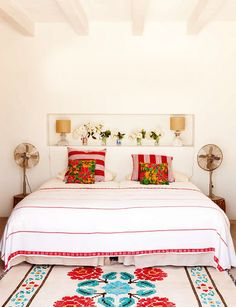 Floral rug in blue and red! Photograph by Gonzalo Machado for Architectural Digest.  Mostly white bedroom with pops of color and vintage fans.