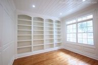 DIY:   Library with White Built-Ins and Wainscoting.  The wainscoting is routered  to order, you just give the company the rooms dimensions.  Image Source