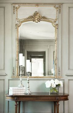 An antique mirror from France is set into the custom paneling of the master bedroom and was the inspiration for the French blue of the room.