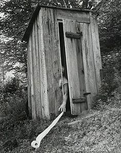 - Person reaching for a toilet paper roll rolling downhill outside an old outhouse, Blue Ridge Mountains, Virginia, USA