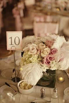 Centerpieces of pale, romantic flowers with ostrich plumes