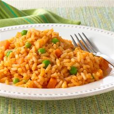 Authentic Mexican rice has a distinctive red-orange color and a slightly smoky, garlic and onion flavor. This popular side dish is made from white rice and typically features vegetables such as peas and carrots.
