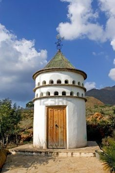 White, cylindrical bird tower or dovecot on sunny Spanish mountainside