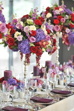Sumptuous purple, red and white roses, pink Cymbidium orchids and purple hydrangeas are set on tall pillars so that guests can see across th...