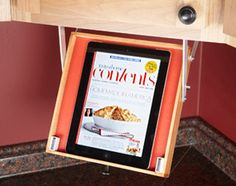 Drop-down tablet tray. Makes it easy to peruse a recipe while working in the kitchen. Could modify the size of the tray so that it will also hold recipe books or other similar items.