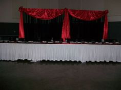 White fitted tablecloth with a satin red runner on top