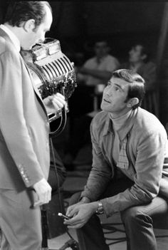 """George Lazenby fiddles with a knife while chatting with director Peter R. Hunt. """"He was a great looking guy and he moved very well,"""" the director, who died in 2002, once said. """"I think if things had gone the other way, he would have gone on to be a very good Bond."""""""