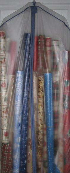 DIY Gift Wrap Organizer : use a clear garment bag for storing gift wrap supplies.