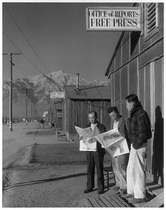 Roy Takeno, editor, and group reading paper in front of office, Manzanar Internment camp for Japanese-American citizens,1943 - Ansel Adams
