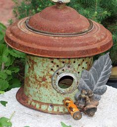 Upcycled Birdhouse.  Materials:  green minnow bucket, ceramic handle, aluminum leaf, wooden vintage pulls, vintage lamp base, vintage lighting parts.