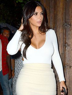 Kim Kardashian keeps her hair in check as she leaves a restaurant in Los Angeles on Wednesday with her husband Kanye West (not pictured).