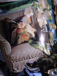 Brown and white striped chair with floral pillow