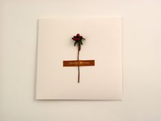 Christmas Wreath - This soft and gentle white folded card has a distinctive felt texture inside and out. Conveying both warmth and high quality. The design features Christmas wreath and a printed 'merry christmas' brown satin ribbon detail on the front of the card. It comes with white envelope in protective cellobag.