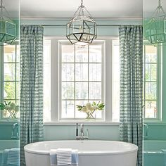 Master Suite: The Bath | A small hallway with two walk-in closets leads into the serene bath, painted a soft blue. Curtains frame a freestanding tub to create a dramatic focal point.