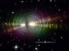 An onionskin-like structure of concentric dust shells surround a central, aging star. Twin beams of light radiate from the star and illuminate the usually invisible dust. Artificial colors show how light reflects off the particles and heads toward Earth.