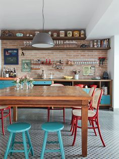 colorful chairs + brick wall texture + wood shelves