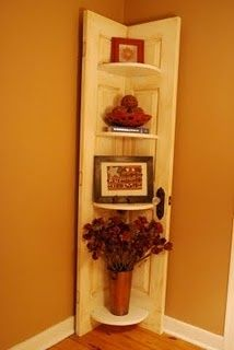 Old door, cut in half, and then reassembled as a corner shelf.  I really like this. You could do this with shutters too I would think.