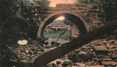 A color tinted photo of the bridge and dam at Lake Park, as seen through the single arch of the old bridge.