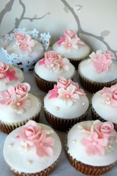 White wedding cupcakes with pink fondant flowers on top